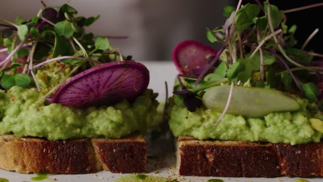 seasoning avocado toast with spices macro shot - pane tostato video stock e b–roll