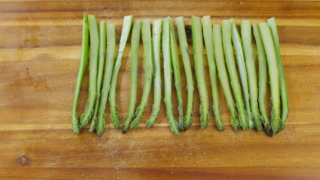 seasoning boiled asparagus on wooden chopping board