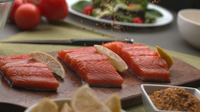 vídeos de stock, filmes e b-roll de tempero cair sobre peixe salmão - formato bruto