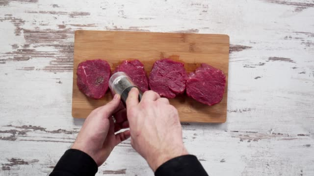 seasoning fresh chunk of the deli piece of beef with sea salt and grounded spicy peppers. video