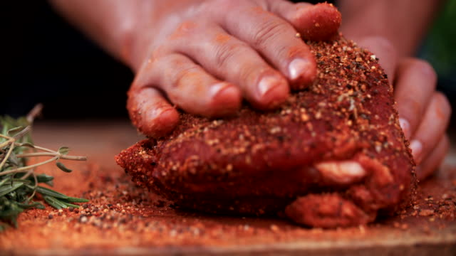 Seasoning of herbs and spices being rubbed into pork Low angle shot of some spicy seasoning being rubbed into a piece of raw pork on a wooden surface with herbs in the foreground spice stock videos & royalty-free footage