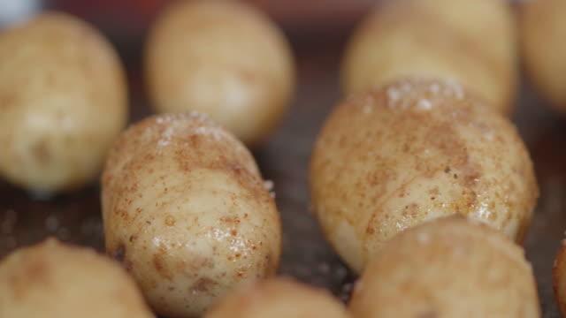 seasoning prepared hasselback potatoes for roasting - молодой картофель стоковые видео и кадры b-roll