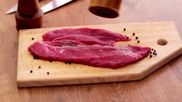 Seasoning steak HD 1080 STATIC: Steak slices being seasoned with pepper using pepper mill on both sides;  jerky stock videos & royalty-free footage