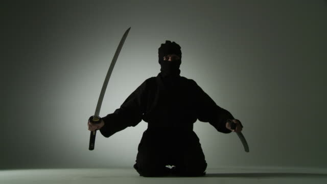 Seated Swordsman Low angle view of a masked ninja unsheathing a short sword, holding it and then re-sheathing it while kneeling on the floor. martial arts stock videos & royalty-free footage