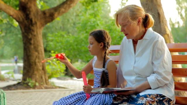 posti a sedere in un parco - nonna e nipote camminare video stock e b–roll