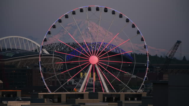 Seattle Hope The Ferris wheel illuminated with a beating heart to support the emergency workers on the frontline of the Covid-19 pandemic with Mount Rainier. 4k stock videos & royalty-free footage