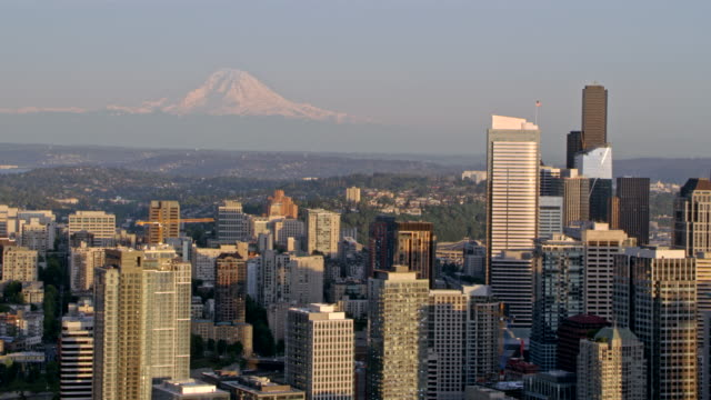 AERIAL Seattle with Mount Rainier in the background Aerial shot of  the city of Seattle with Mount Rainier seen in the distance. Shot in WA, USA. seattle stock videos & royalty-free footage