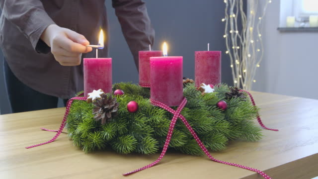 Second Sunday of Advent - a young woman is lighting the second candle of the advent wreath video