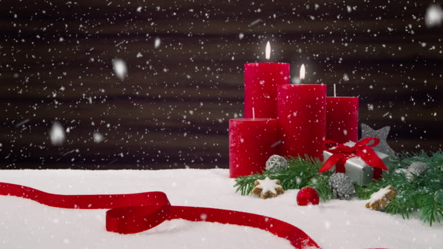 Second Sunday of Advent - Beautiful snowfall in front of a Christmas decoration arrangement on a snowy table in front of a wooden background video