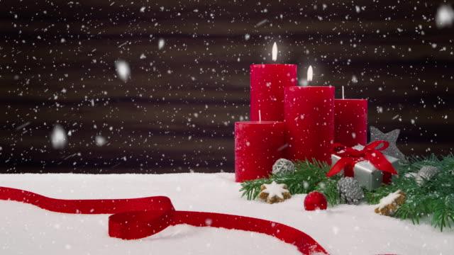 2. Sonntag im Advent - schönen Schneefall vor ein Weihnachtsarrangement Dekoration auf einem verschneiten Tisch vor einem hölzernen Hintergrund – Video