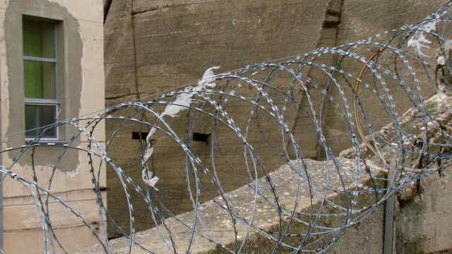 secret facility behind a concrete wall and barbed wire video