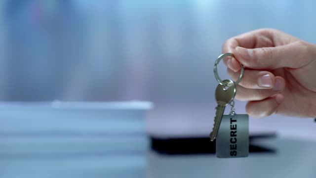 Secret written on keychain lady taking from hand, censored information, protect