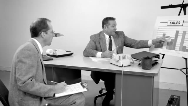 Secretary brings coffee and papers to business man in meeeting video