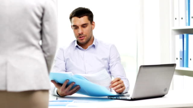 secretary or assistant and businessman with documents in folder at office