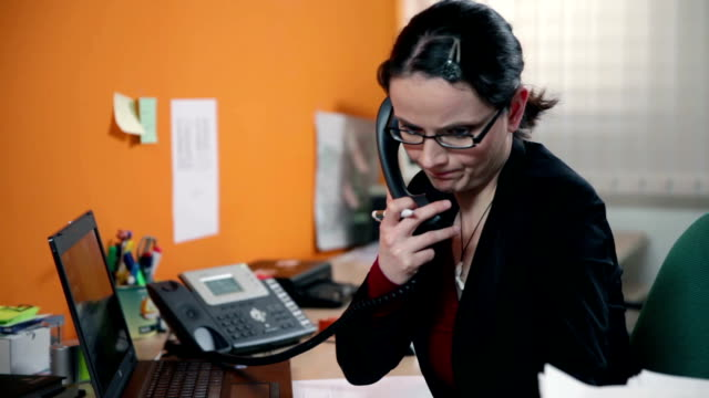 HD STOCK: Secretary talking on a phone in her office video