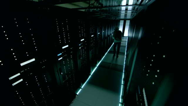 Security Camera Footage of Hacker in a Hoodie Inflitrating Data Center, With His Laptop He Connects to One of The Rack Servers. video