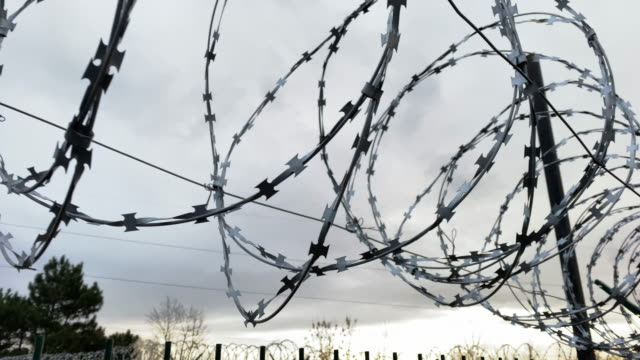 Security fence with razor wire on border of the object at dawn.