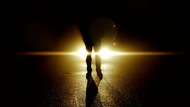 security guard at night shift working in the street. back lit by car lights. - podświetlony filmów i materiałów b-roll