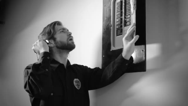 Security guard checking circuit breaker A security guard opens a circuit breaker panel and checks for faults while holding a flashlight. futebol stock videos & royalty-free footage