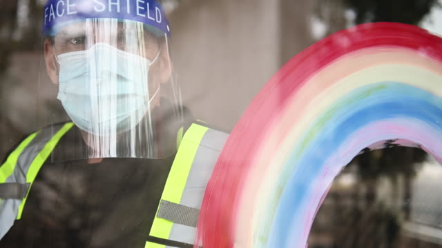 security guard covid-19 mask and face shield and gloves on and rainbow symbol - essential workers stock videos & royalty-free footage