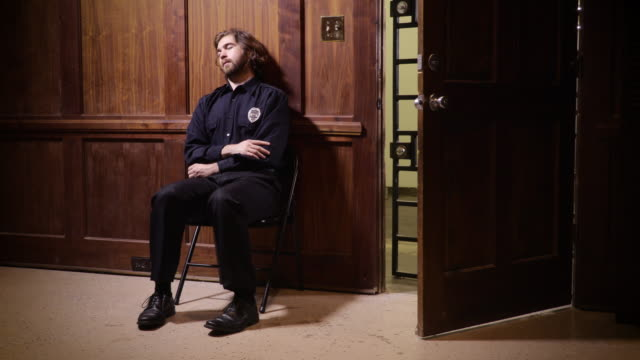 Security guard sleeping by open door A security guard falls asleep in a folding chair at his post. The door next to him is open and unlocked. security staff stock videos & royalty-free footage