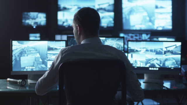 Security officer is drinking coffee while working on a computer in a dark monitoring room filled with display screens.