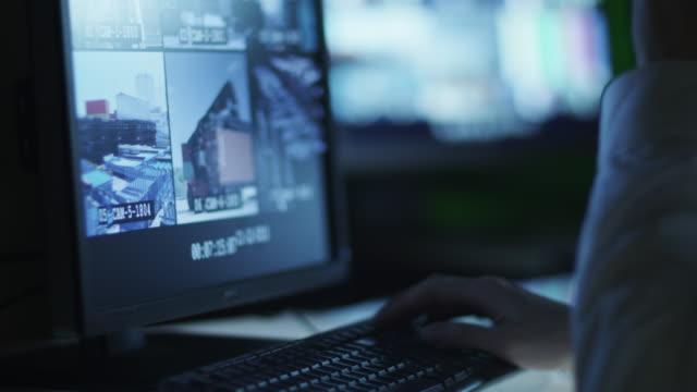 security officer ist überwachung displays im kontrollraum am abend mit tasse kaffee - überwachungskamera stock-videos und b-roll-filmmaterial