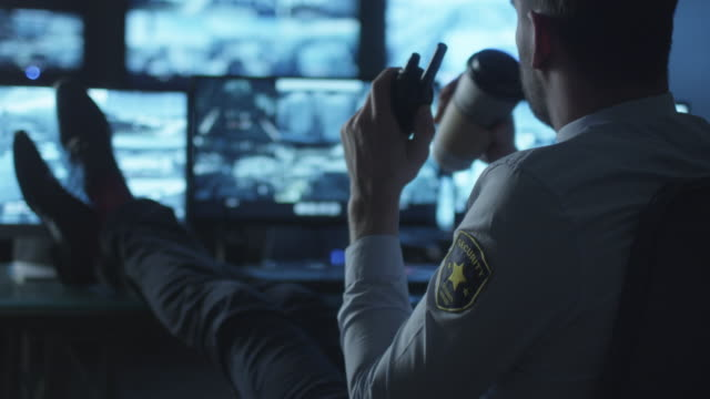 Security officer is relaxing at a computer desk while drinking coffee in a dark monitoring room filled with display screens. video