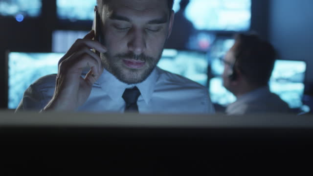 Security officer is talking on the phone while working on a computer in a dark monitoring room filled with display screens. video
