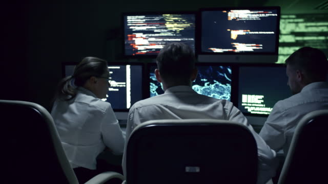 IT Security Professionals Working at Night Rear view of three IT specialists discussing cyber security at desk in front of multi-display workstation in dark office at night encryption stock videos & royalty-free footage