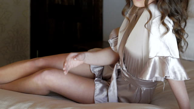 Seductive girl in nighty posing on the bed. Slowly video