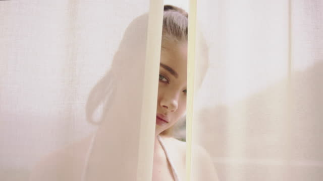 Seductive woman hiding behind transparent curtain
