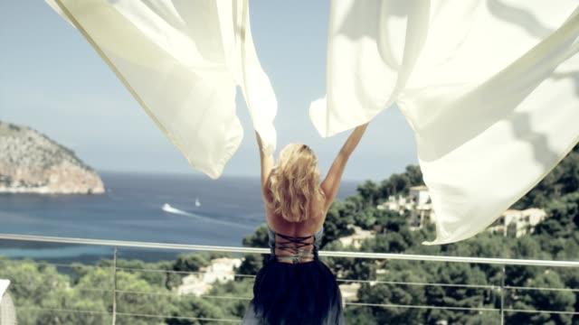 stockvideo's en b-roll-footage met verleidelijke vrouw in elegante jurk u geniet van het uitzicht - bewondering