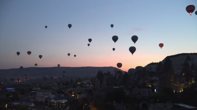 see Hot Air Balloons start  Flying before Sunrise from city, Cappadocia, Turkey