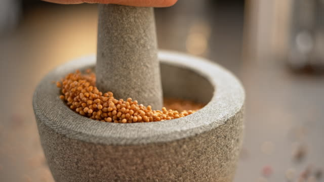 SLO MO LD Seeds being crushed in the mortar with a granite pestle