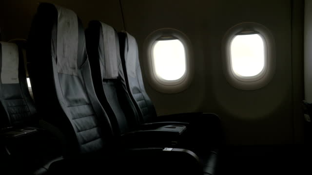 seen interior decor of plane - black leather chairs and two portholes - sedili aereo video stock e b–roll