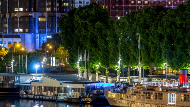 Seine river with ship in Paris at night timelapse, waterfront of the seine river in the city of Paris in france video