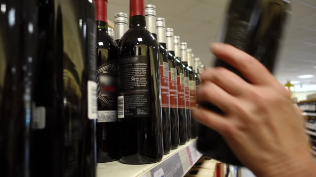 selecting wine bottle from shelf. - alchol video stock e b–roll