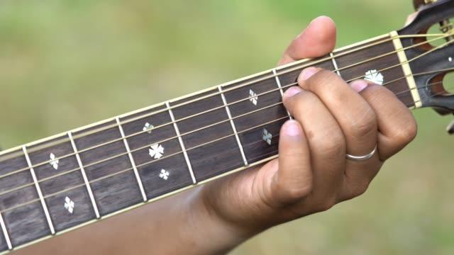 vídeos de stock, filmes e b-roll de o foco seletivo 4k fecha-se acima do tiro da mão do homem novo que joga as cordas de bronze uma guitarra acústica na guitarra da garganta. o músico aperta os acordes na guitarra. - música acústica