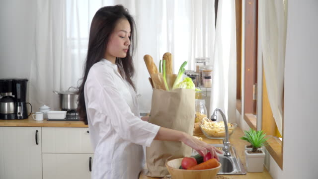 4K Selective focus medium shot of happy relax asian young woman in white shirt holding groceries paper bag into kitchen. Teenage girl unpacking vegetables and fruits from supermarket shopping bag.