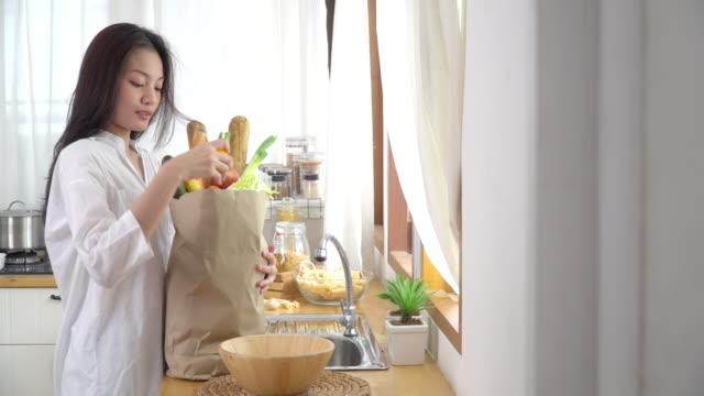 4k tiro medio a fuoco selettivo di felice relax giovane donna asiatica in camicia bianca che tiene il sacchetto di carta della spesa in cucina. adolescente che spacchetta verdure e frutta dalla borsa della spesa del supermercato. - grocery home video stock e b–roll