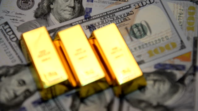 Selective focus of gold bars and dollars on a table Selective focus of gold bars and dollars on a table. gold bars stock videos & royalty-free footage