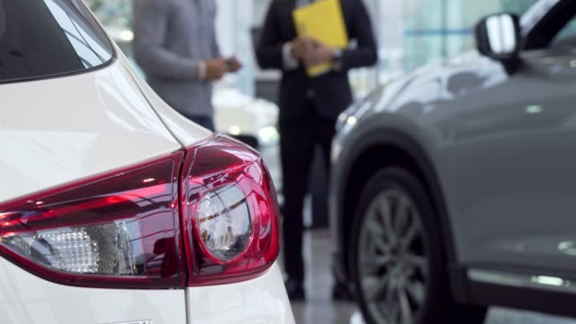Selective focus on a car, salesman talking to the customer on the background Selective focus on a car, salesman talking to the customer on the background. New automobile on foreground, man choosing new auto at the dealership. Driving concept car salesperson stock videos & royalty-free footage
