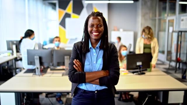 カメラと笑顔を見ているオフィスで自信を持って女性 - 上半身点の映像素材/bロール