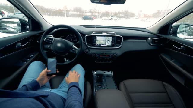 自動運転自動操縦自律走行車。携帯電話を持つ男性運転手は、自動的に駆動される車を駐車しています - 自動運転車点の映像素材/bロール