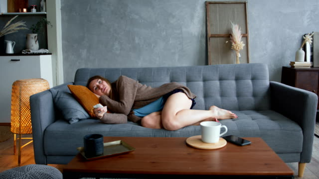 self isolation and depression. young beautiful caucasian woman lying down on sofa tired of watching tv at home alone. - divano procrastinazione video stock e b–roll