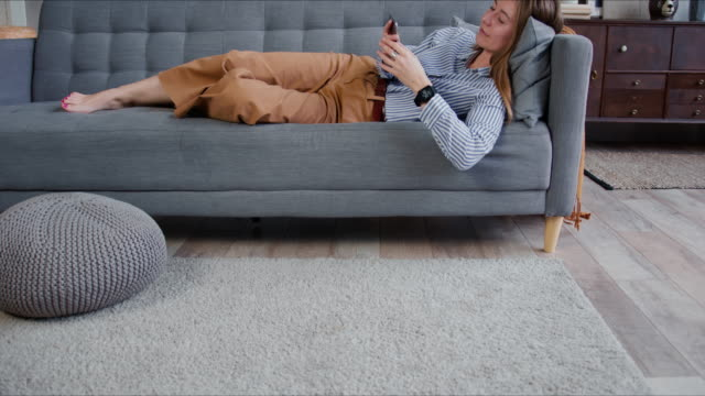 self isolation concept. young relaxed beautiful blonde woman scrolling feeds on smart phone, smiling at camera on sofa. - divano procrastinazione video stock e b–roll