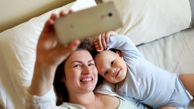 stockvideo's en b-roll-footage met zelf moeder en baby in bed in de vroege ochtend. concept van het gelukkige moederschap, mother's day - video's van baby
