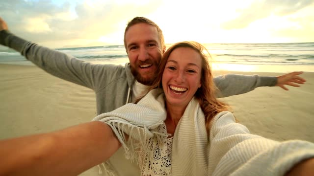 vídeos de stock e filmes b-roll de self portrait of happy young couple on beach at sunset - selfie