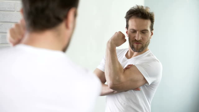 Self-affected macho looking in mirror at his muscles and biceps after workout video